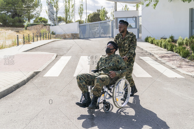 Army officer helping another military soldier sitting on wheelchair