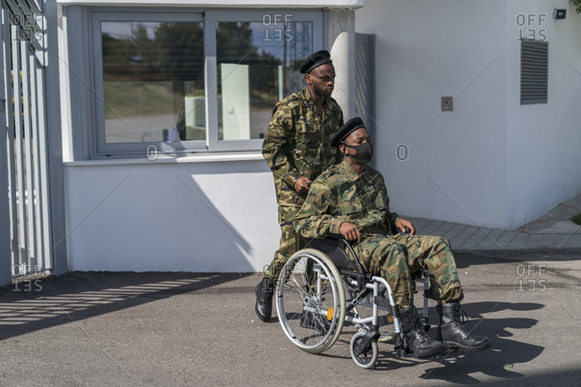 Army soldier helping military officer while pushing wheelchair