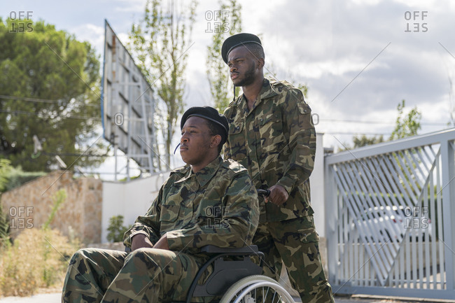 Serious army soldier helping another military officer sitting on wheelchair