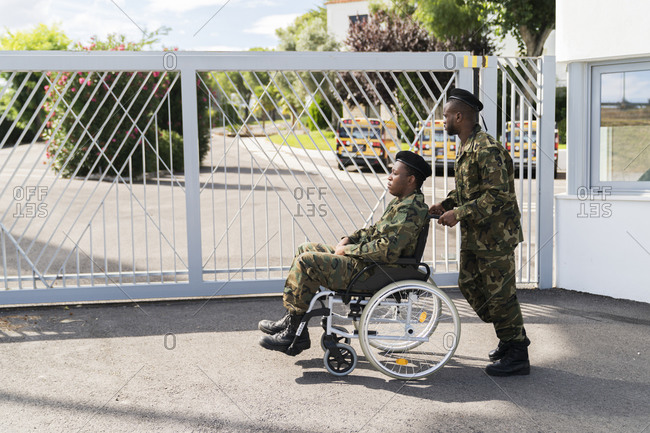 Army soldier pushing military soldier on wheelchair while standing against gate