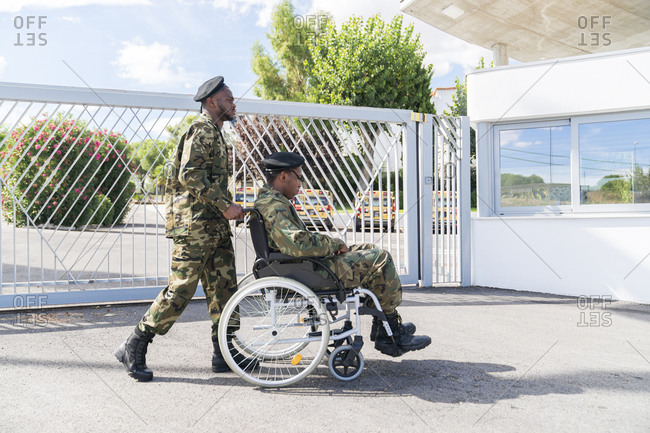 Army soldier helping military soldier on wheelchair while standing against gate on sunny day