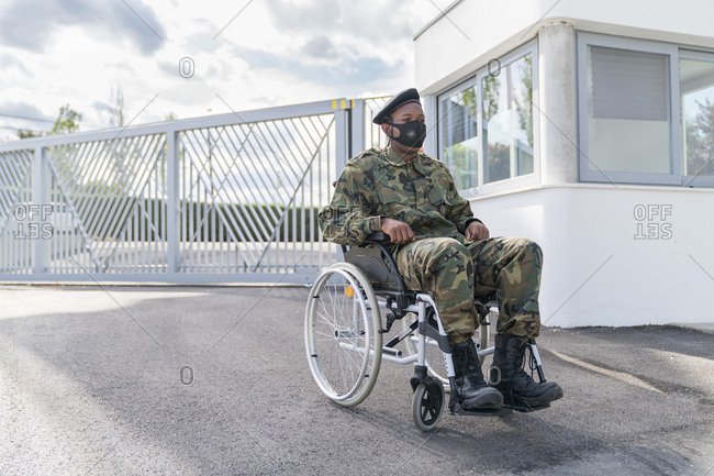 Army soldier with protective face mask sitting on wheelchair