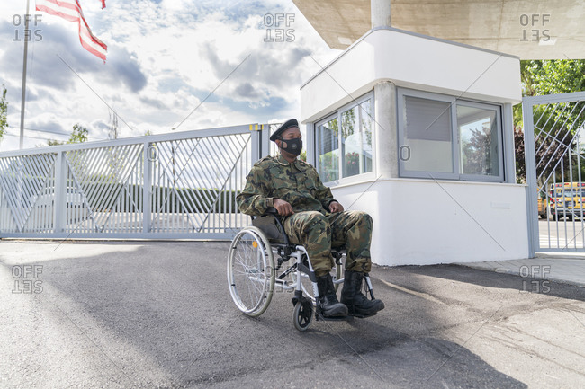 Army soldier with protective face mask sitting on wheelchair against cloudy sky