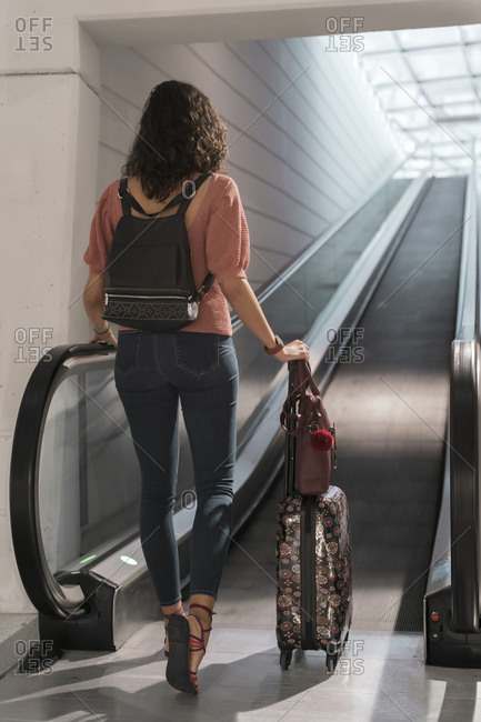Young woman with suitcase moving towards walkway at airport