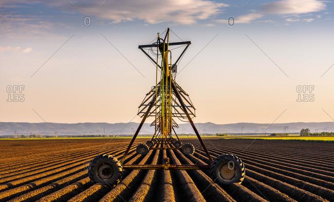 Agricultural sprinkler on field during sunset