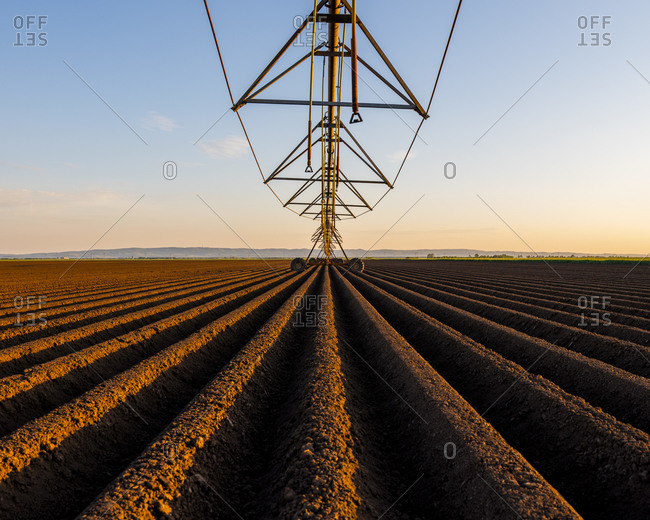 Agricultural machinery in ploughed field against sky during sunset
