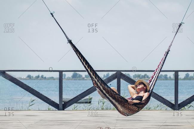Relaxed woman lying in hammock on boardwalk by sea against clear sky