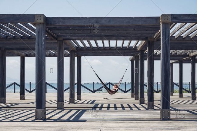 Woman lying in hammock hanging from metallic structure on boardwalk during sunny day