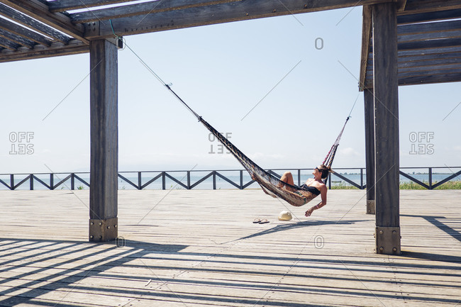 Relaxed woman lying in hammock hanging from metallic structure on boardwalk during sunny day