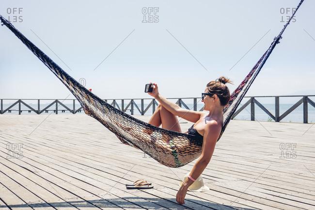 Beautiful woman taking selfie through smart phone while lying in hammock on boardwalk