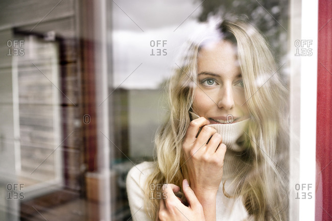 Close-up of businesswoman wearing turtleneck looking through window from office seen through glass