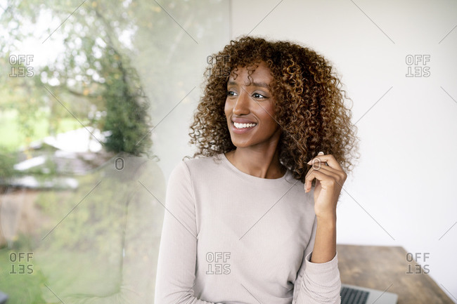 Thoughtful female professional with curly hair looking through window in office