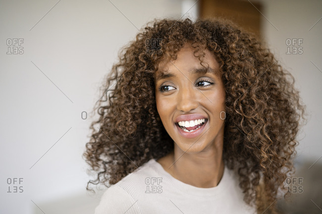 Close-up of cheerful businesswoman with curly hair looking away against wall in office