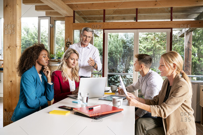 Manager discussing business strategy with colleagues over laptop in meeting at office