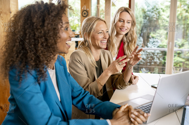 Cheerful female coworkers discussing business strategy at desk in office