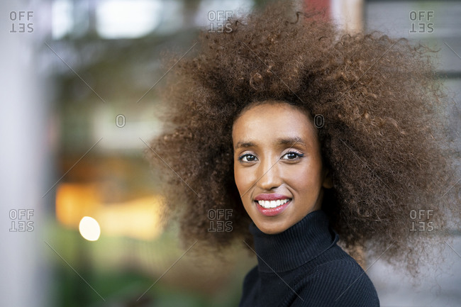 Close-up of smiling businesswoman with curly frizzy hair