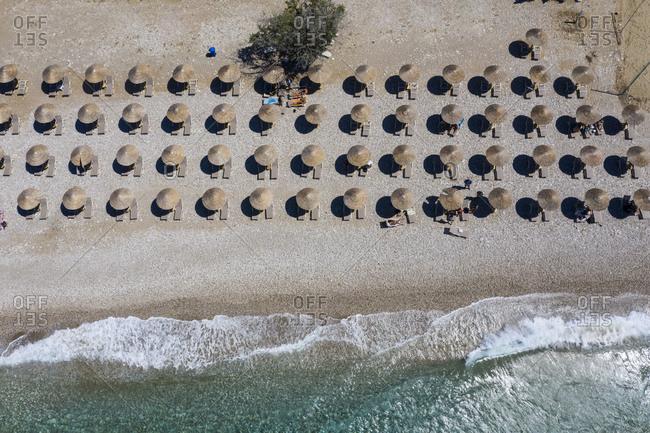 Rows of deck chairs and beach umbrellas along Potami Beach in summer