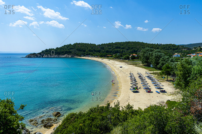 Greece- Sithonia- Umbrellas and deck chairs along sandy coastal beach in summer