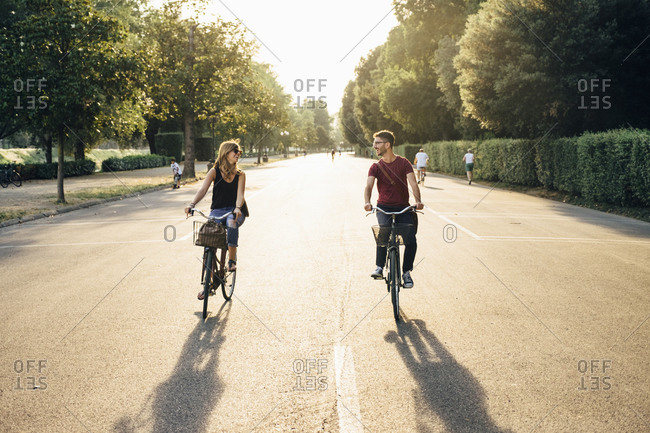Happy couple cycling on road amidst trees in park during sunset