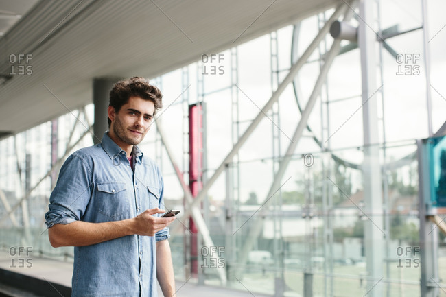Confident casual businessman using smart phone while standing ta railroad station