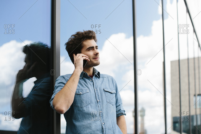 Casual businessman talking over smart phone while standing against modern building