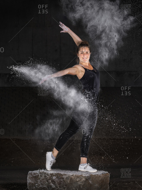 Young woman dancing with flour against wall