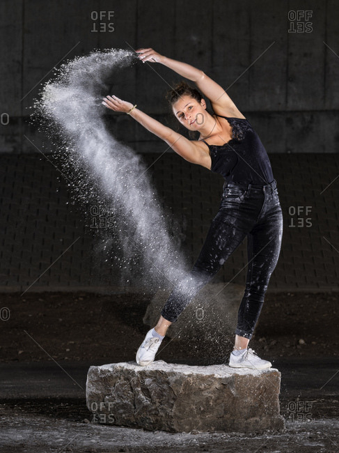 Young woman splashing flour while dancing against wall
