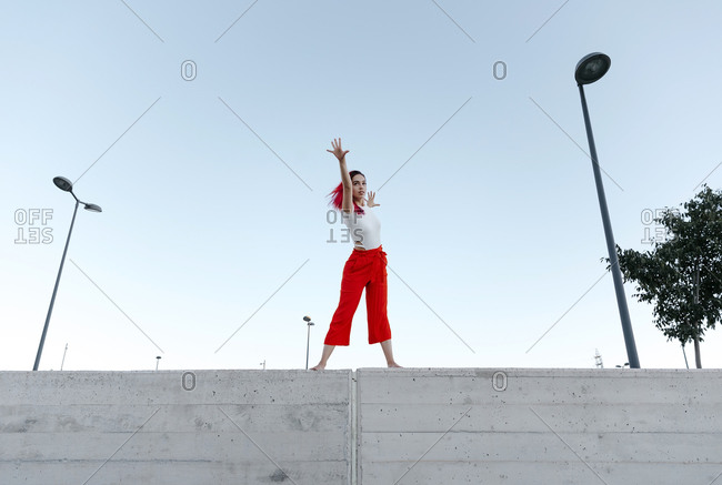 Woman wearing red pant dancing on wall against clear sky
