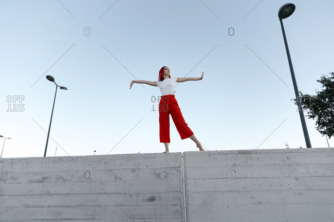 Young dancer with arms outstretched standing on surrounding wall against clear sky