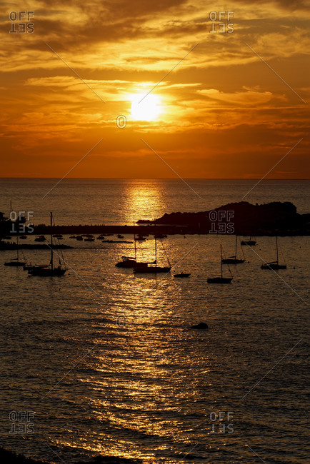 France- Haute-Corse- Lille-Rousse- Silhouettes of sailboats in front of small Mediterranean island at moody sunset