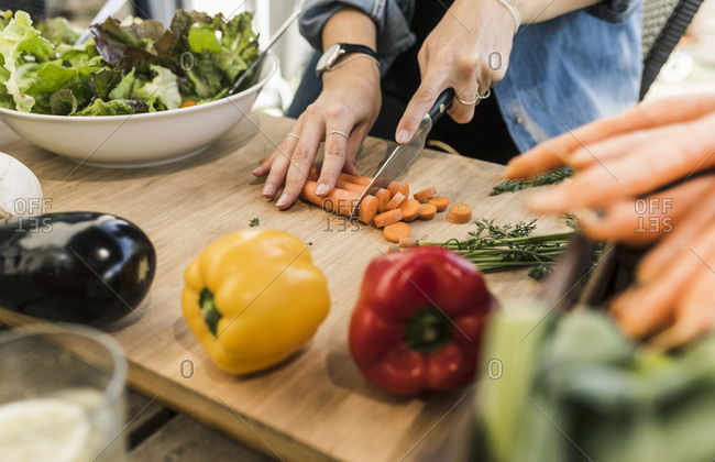 Close-up of young woman chopping carrots on cutting board