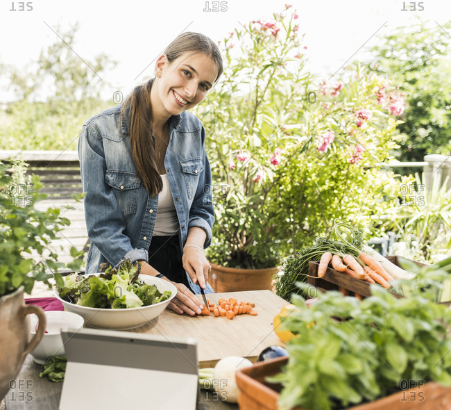 Smiling woman chopping vegetables on cutting board in yard