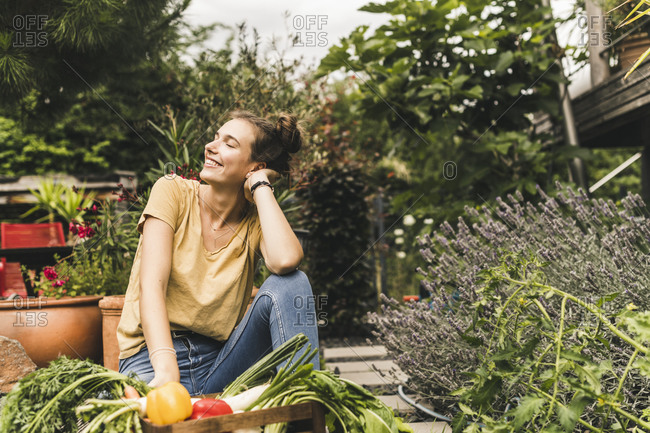 Young woman with eyes closed sitting by vegetables and plants in community garden