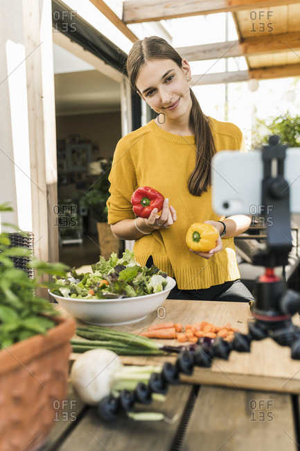 Smiling woman filming with mobile phone while preparing food at home