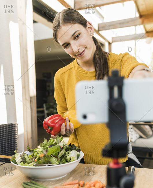Smiling young woman adjusting smart phone on tripod while filming at home