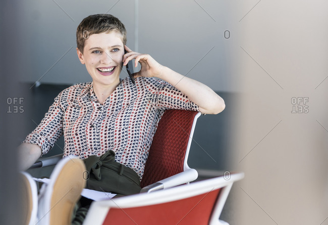 Happy businesswoman sitting on office chair talking on the phone