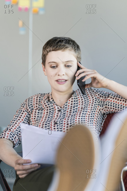 Businesswoman sitting on office chair talking on the phone