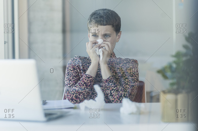 Ill businesswoman at desk in office blowing nose