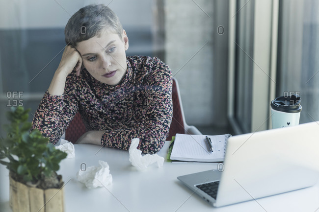 Ill businesswoman at desk in office
