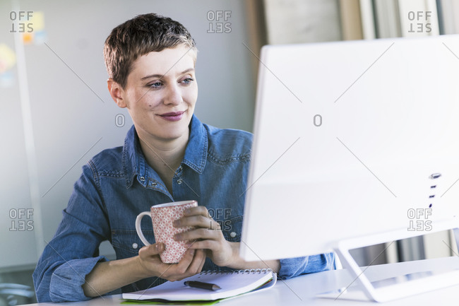 Smiling businesswoman at desk in office looking at computer screen
