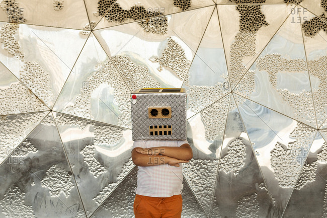 Boy wearing robot mask with arms crossed standing against patterned silver wall