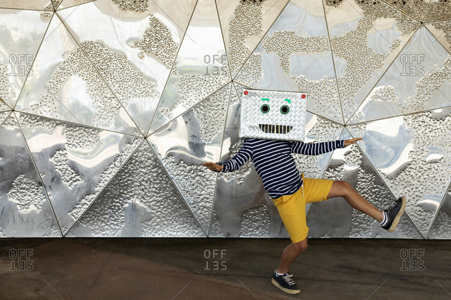 Boy wearing robot mask dancing on footpath against patterned wall