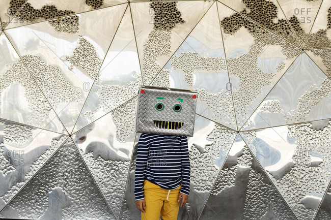 Boy wearing robot mask standing against silver patterned wall