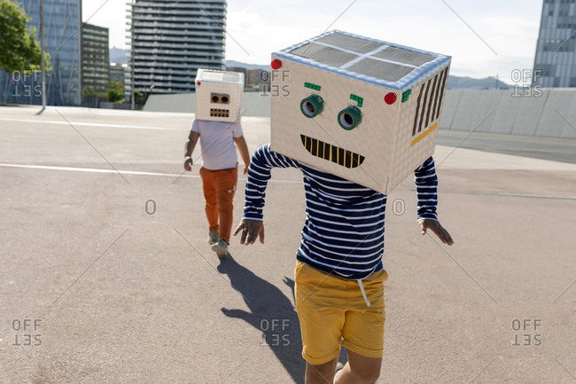 Carefree boy wearing robot mask dancing while friend walking on street in city