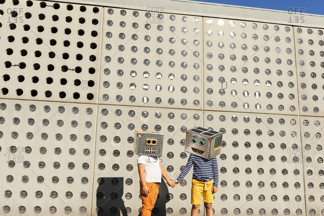 Friends wearing robot costumes holding hands while standing against wall on sunny day