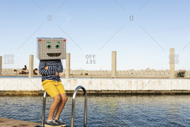 Boy wearing robot mask made of box while sitting on railing by the water against clear sky
