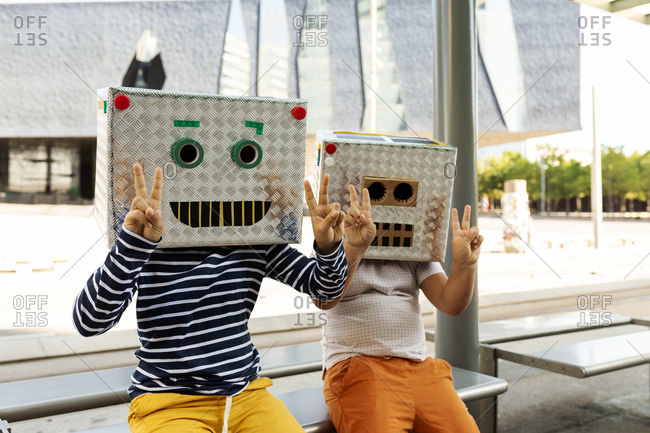 Boys wearing robot masks showing peace sign while sitting on seat at railroad station