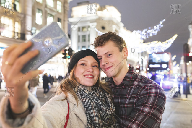 Woman taking selfie with boyfriend against Christmas lights in city at night