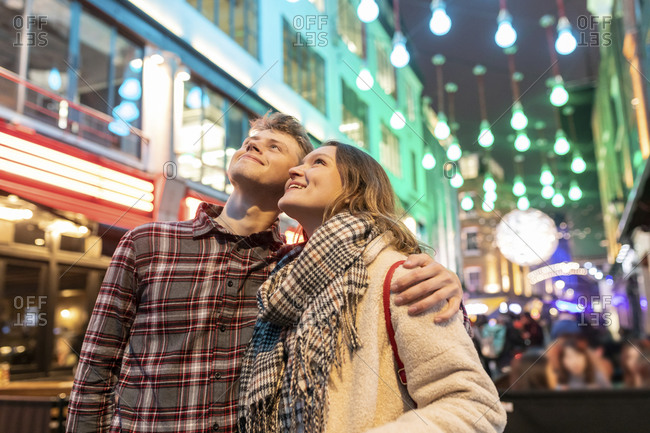 Smiling young couple looking up while standing against Christmas lights in city