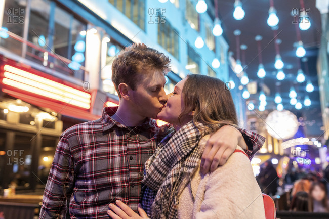 Romantic young couple kissing while standing against Christmas lights in city at night